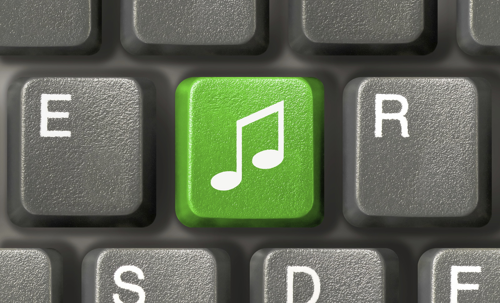 Computer keyboard (close-up) with green music key